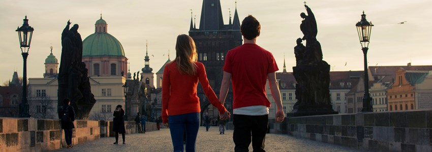 Loving couple walking down the Charles Bridge in Prague at sunset