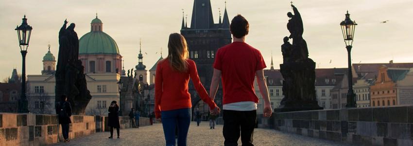 Loving couple walking down the Charles Bridge in Prague at sunset