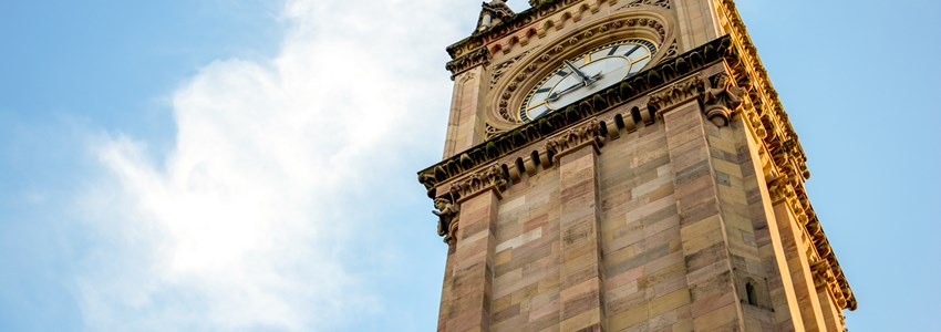 Albert Memorial Clock tower in Belfast in Northern Ireland with blie sky in the background