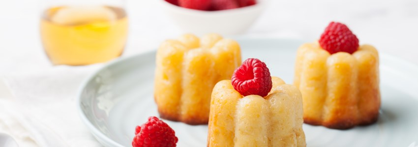 French dessert, cakes, caneles, rum baba with fresh raspberry and dessert wine on a white background