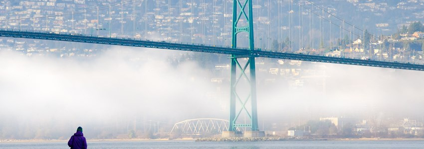 A foggy winter day in Vancouver, British Columbia, Canada, as seen from the seawall in Stanley Park, with the Lions Gate Bridge and North Shore Mountains in the background.