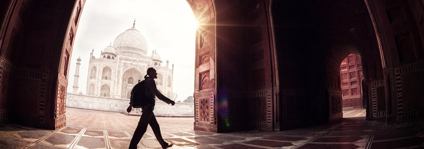 Tourist with backpack walking in the mosque arch near Taj Mahal in Agra, Uttar Pradesh, India