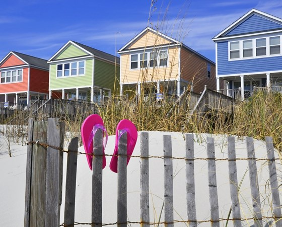 Row of beach rentals on a summer day, pink flip flops on beach fence