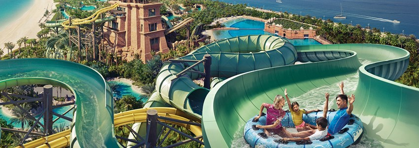 happy family slides down a waterslide in an inflatable