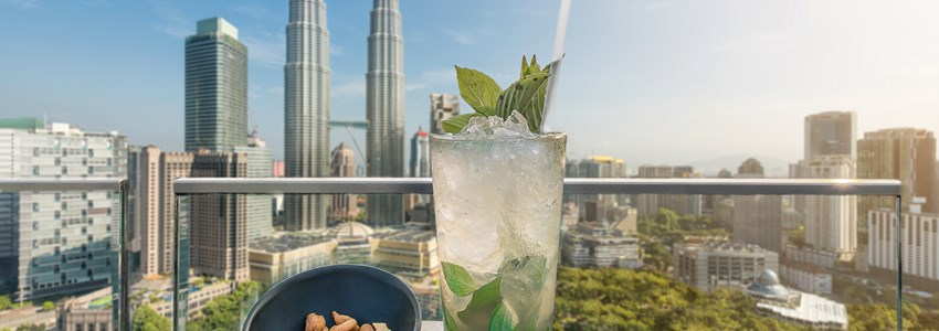 Mojito cocktail and cashews on table in rooftop bar at Kuala Lumpur, Malaysia