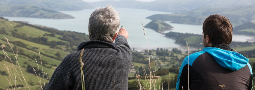 Two men sit on the top of hill and look at harbour, New Zealand