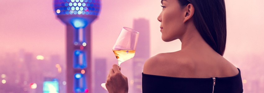 Woman with drink overlooking Oriental Tower