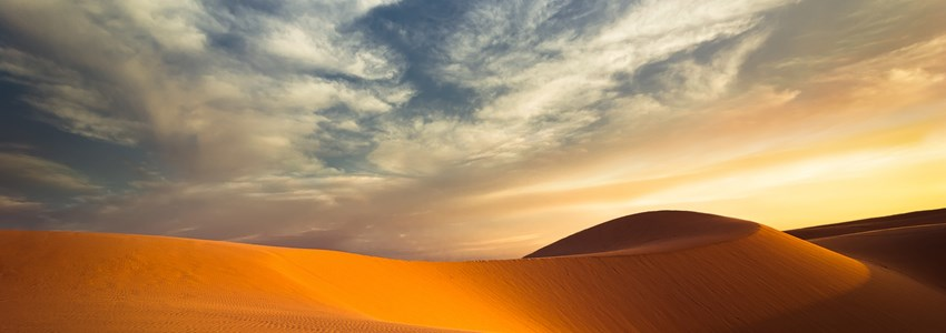 Global warming concept. Lonely sand dunes under dramatic evening sunset sky at drought desert landscape