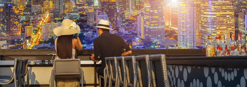 Asian lover couple enjoying look at view twilight time on top view bar and restaurant in this time beautiful colorful night at Bangkok City
