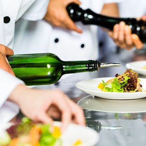 chef along with other cooks in restaurant or hotel commercial kitchen cooking, finishing dish or plate / Kzenon/Shutterstock.com