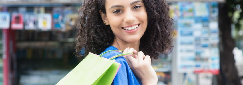 Laughing latin american woman with shopping bags
