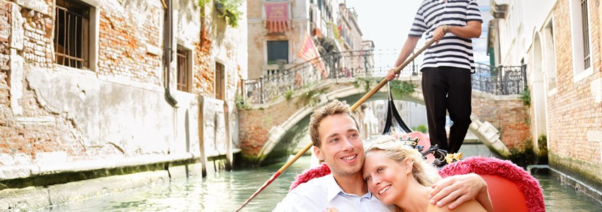 Romantic young beautiful couple sailing in venetian canal in gondola. Italy, Europe.