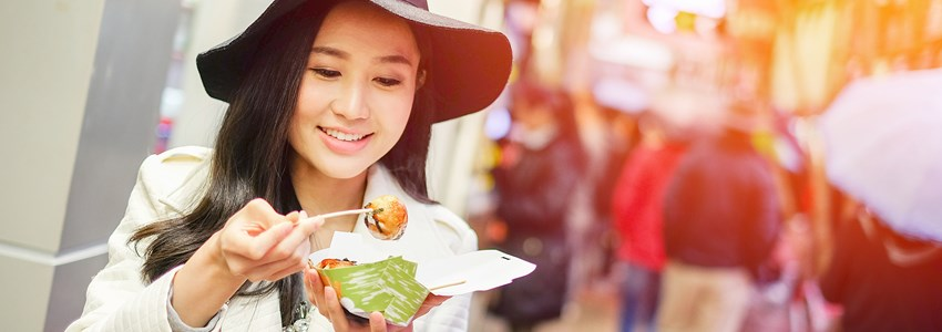 Chinese Asian young female model eating dumpling batter (Takoyaki) on Street in Hong Kong