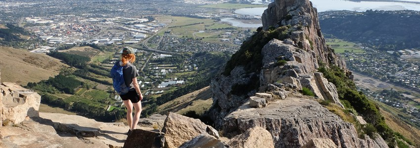Woman Hiker Ascending Castle Rock. Port Hills, Christchurch, New Zealand.