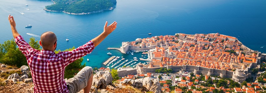 man with opened arms sitting on the edge of a cliff, looking down to the Old Town of Dubrovnik, Croatia