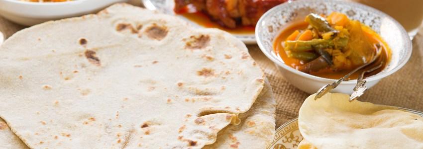 Chapatti roti or Flat bread, curry chicken, biryani rice, salad, masala milk tea and papadom. Indian food on dining table.