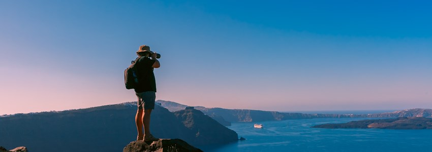 Photographer traveler takes picture caldera and Santorini island in Aegean sea, Greece