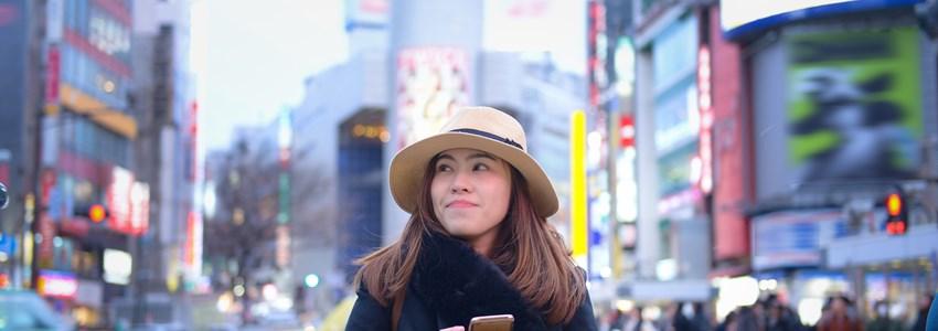 Woman tourist is using smart phone at Shibuya cross walk junction.