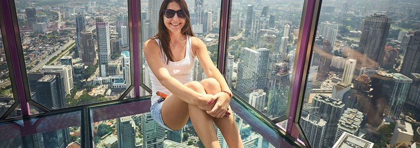 Young woman sitting on the transparent glass floor in Menara KL tower, Kuala Lumpur