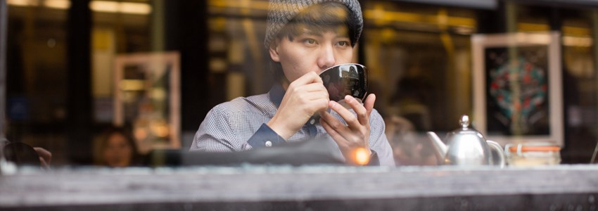 Young asian male drinking tea in cafe whilst looking out of window.