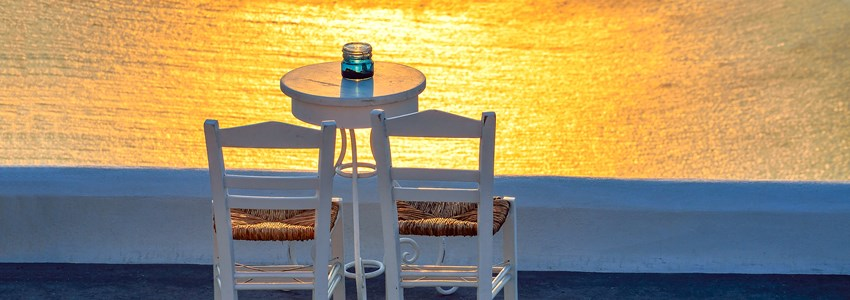 Two chairs and a small table with a wonderful view in Santorini, Greece.