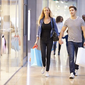 Happy Couple Carrying Bags In Shopping Mall / Monkey Business Images/Shutterstock.com