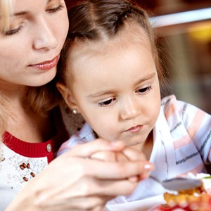 Portrait of cute girl eating cupcake with her mother near by in cafe / Pressmaster/Shutterstock.com