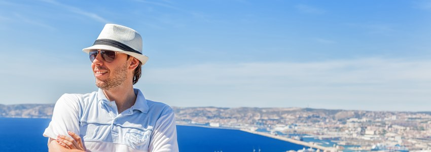 Happy traveling! Handsome man in a hat and sunglasses posing against the city of Marseille