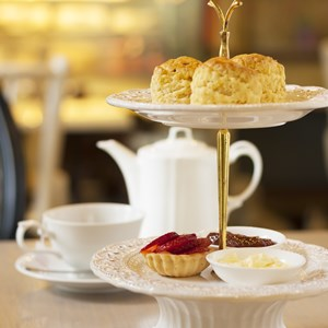 scones on two tiered tray with teapot and cup background / Atiketta Sangasaeng/Shutterstock.com