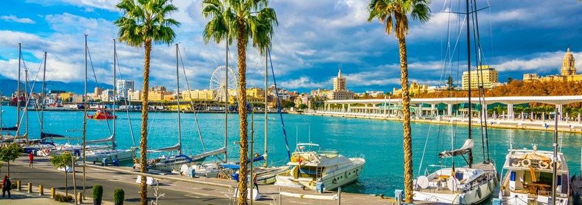 people are walking on a promenade surrounded by marina in the port of malaga in spain.