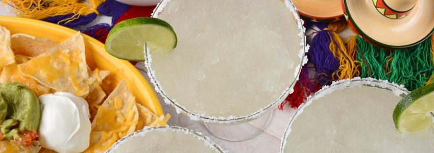 High angle view of three margarita cocktails surrounded by nachos