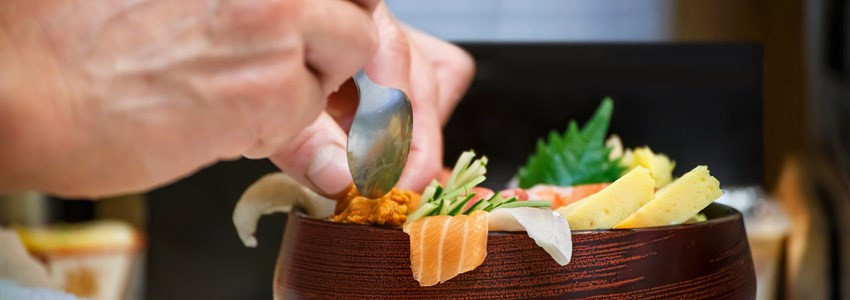 Closeup of a bowl of Sashimi with hands of Japanese chef