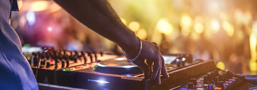 Dj mixing outdoor at beach party festival with crowd of people in background - Summer nightlife view of disco club outside - Soft focus on hand - Fun, youth, entertainment and fest concept - Bild