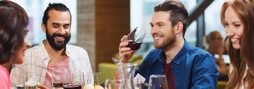 friends dining and drinking wine at restaurant