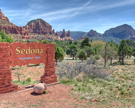 Welcome Sign To Sedona Arizona With A Scenic Background